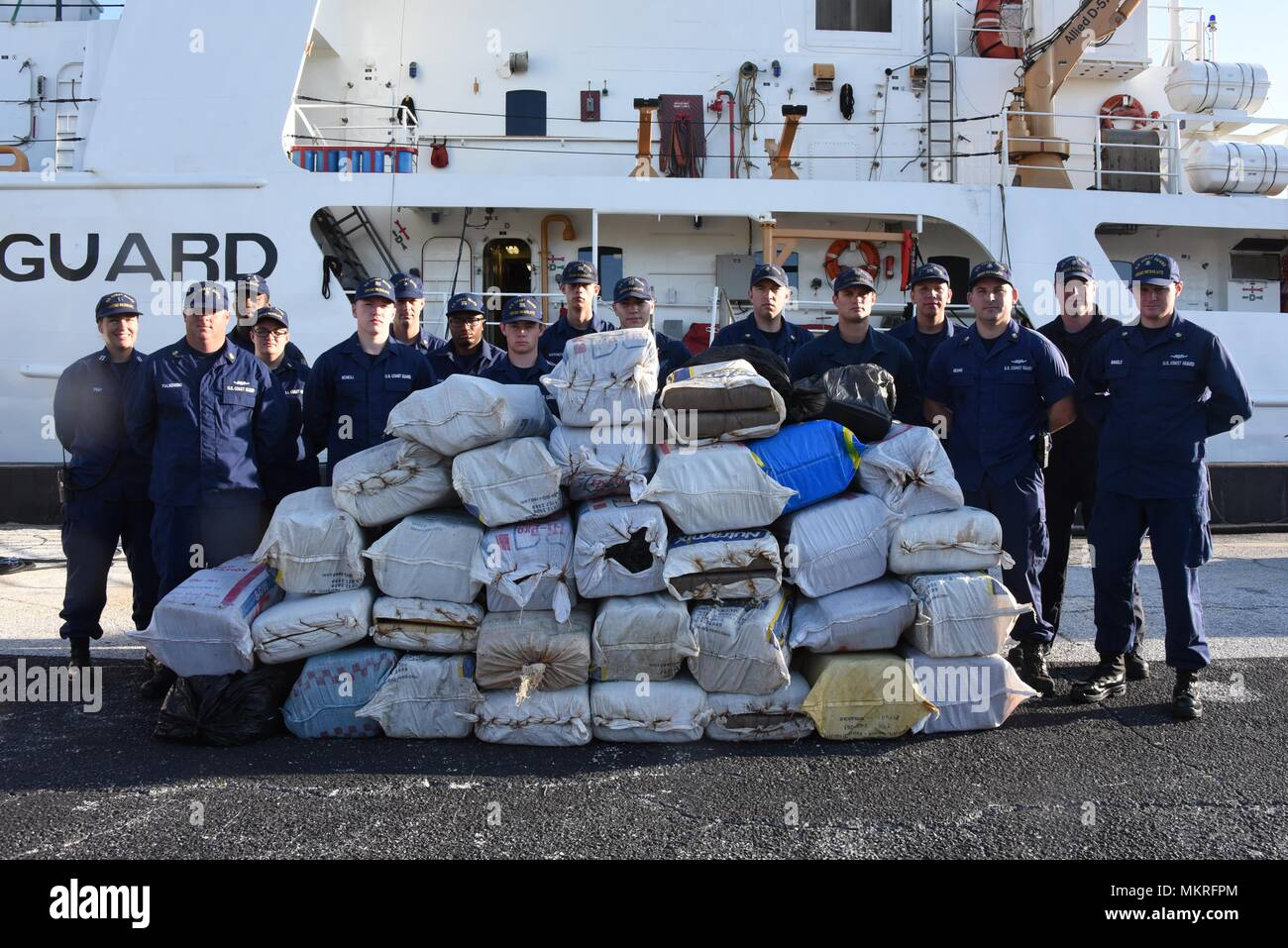Coast Guard Cutter Resolute crewmembers stand next to approximately 1 ton of marijuana worth an estimated $2.2 million wholesale value, in St. Petersburg, Florida, Tuesday, May 8, 2018, May 8, 2018. The crew aboard the 210-foot Reliance-class cutter, homeported in St. Petersburg, offloaded the drugs after interdicting two suspected drug smuggling vessels and detaining seven suspected drug smugglers in the Caribbean Sea with the assistance of Customs and Border Patrol as part of Operation Riptide. (U.S. Coast Guard photo by Petty Officer 2nd Class Ashley J. Johnson). () - Stock Image
