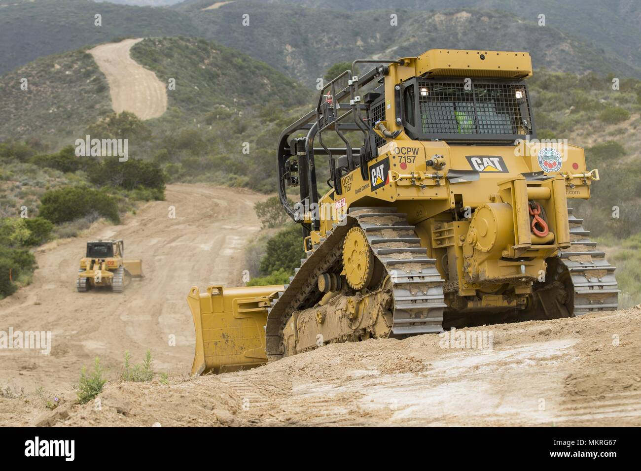 Camp Pendleton, CAL Fire, and Orange County Firefighters excavate fire breaks for the second day in a row during joint operations on Camp Pendleton, Calif. May 1, 2018, May, 2018. The goal is to establish 38 miles of a total 164 miles of firebreaks used to keep fires from leaving the installation and damaging property on and off base for the rest of the fire season. Neighboring Fire Departments use Camp Pendleton's fire fighting operations as a resource for training and improving tactics that they wouldn't otherwise implement. (U.S. Marine Corps photo by Lance Cpl. Betzabeth Y. Galvan). () - Stock Image