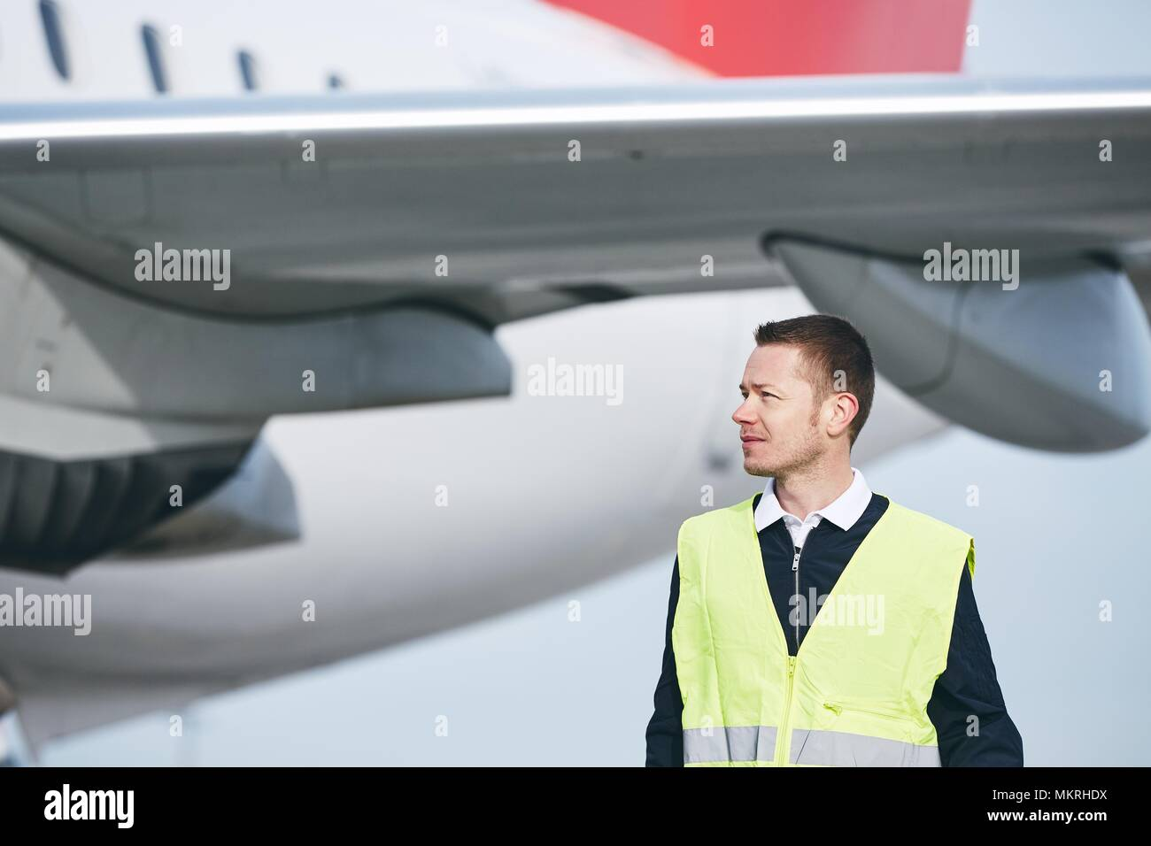 Member ground crew worker at the airport checking airplane before flight. - Stock Image