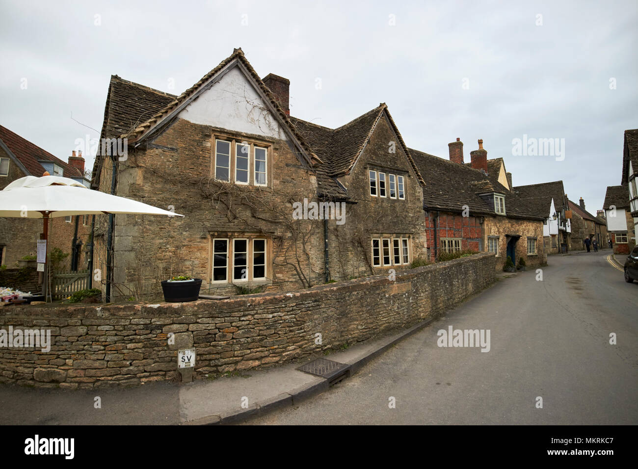 the corner house at the entrance to church street late medieval building Lacock village wiltshire england uk - Stock Image