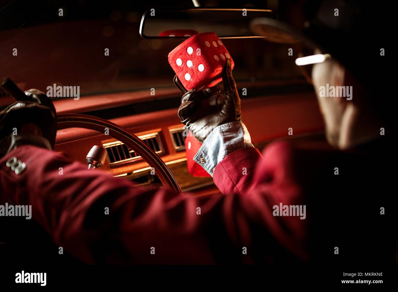 Casino Lucky Wish Concept. Casino Poker Player Talking to His Lucky Red Dice Inside the Classic Car. - Stock Image