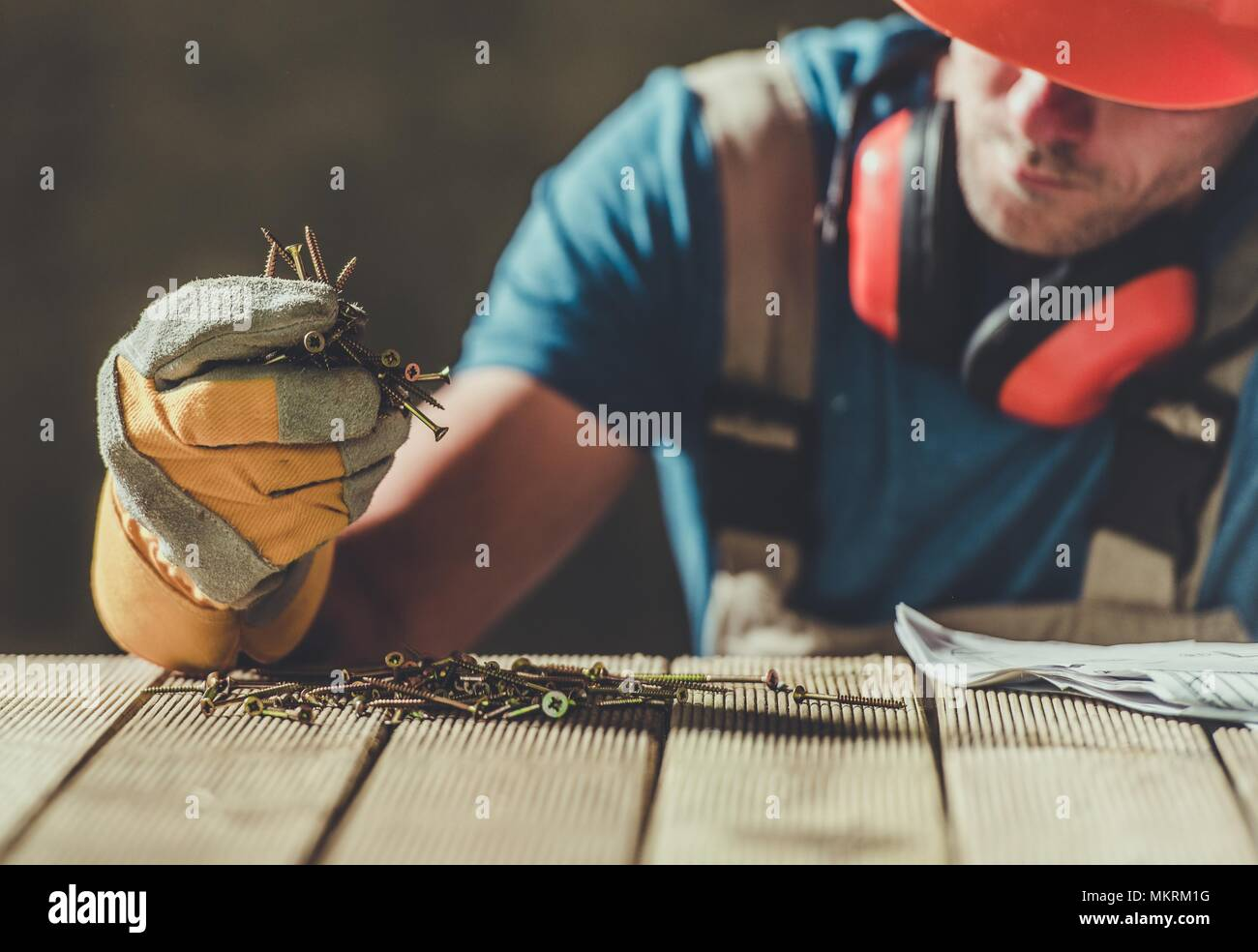 Caucasian Construction Worker with the Wood Screws. Taking Moment to Rethink the Job and the Life. - Stock Image