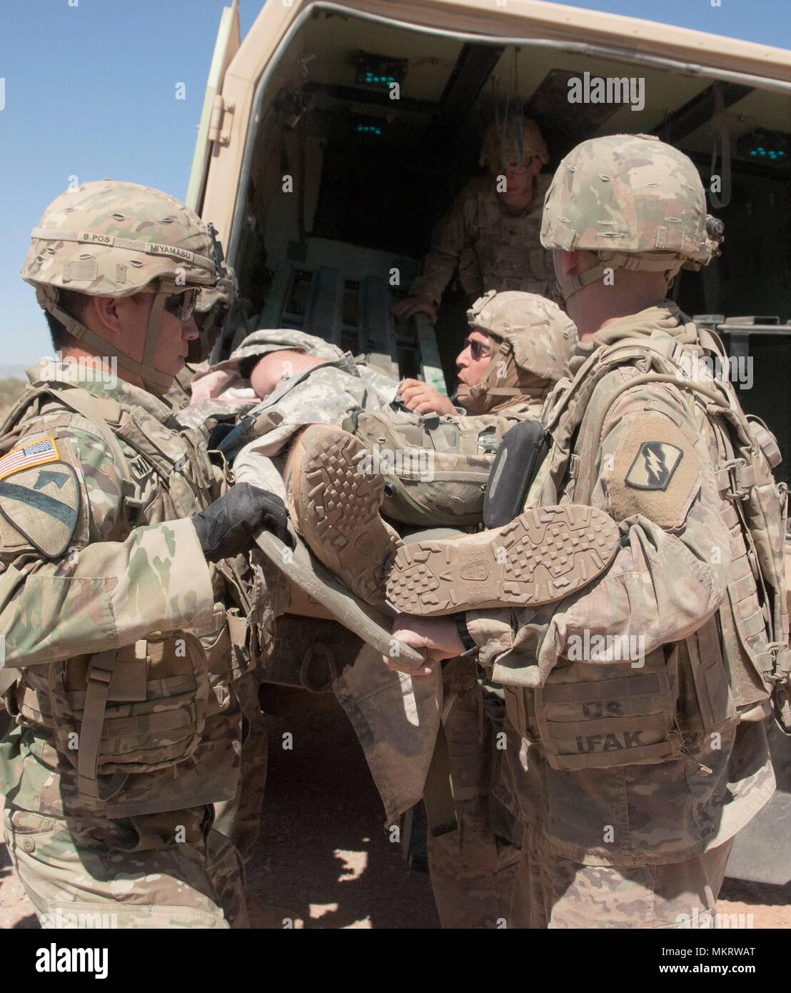 Field medics load a casualty into a Field Litter Ambulance to be transported to the Roll 2 triage center during the MASCAL exercise on McGregor Training Complex, New Mexico, May 4, May 8, 2018. The training was part of the Multi-Echelon Integrated Brigade Training that the 155th ABCT is currently undergoing to prepare for its upcoming deployment in support of Operation Spartan Shield. () - Stock Image