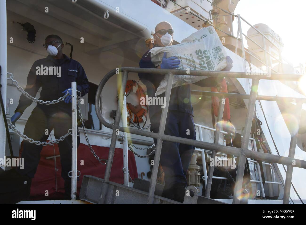 Coast Guard Cutter Resolute crewmembers offload approximately 1 ton of marijuana worth an estimated $2.2 million wholesale value, in St. Petersburg, Florida, Tuesday, May 8, 2018, May 8, 2018. The crew aboard the 210-foot Reliance-class cutter, homeported in St. Petersburg, interdicted two suspected drug smuggling vessels and detained seven suspected drug smugglers in the Caribbean Sea with the assistance of Customs and Border Patrol as part of Operation Riptide. (U.S. Coast Guard photo by Petty Officer 2nd Class Ashley J. Johnson). () - Stock Image