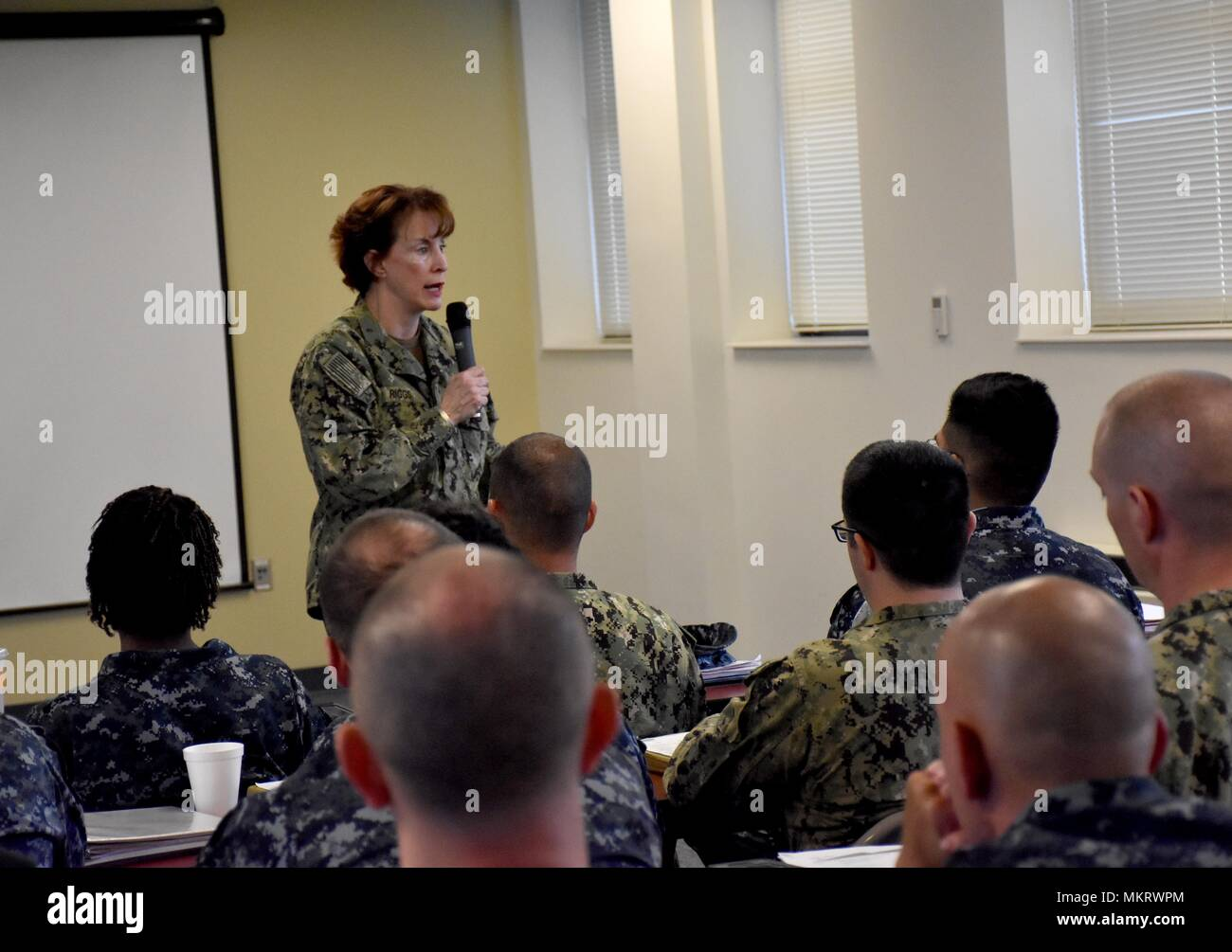 Norfolk, Va. (May 7, 2018) Rear Admiral Mary Riggs, Director, Research and Development, Defense Health Agency speaks at Expeditionary Combat Readiness Centers (ECRC) to members of Expeditionary Medical Unit (EMU) 5 prior to their deployment, May 7, 2018. ECRC provides processing, equipping, training, certification and proactive family support to ADSW Sailors, Individual Augmentees and provisional units throughout all deployment phases in support of combatant commanders requirements, contingency operations, or national crises. (U.S. Navy photo by Chief Mass Communication Specialist James C. Bro - Stock Image