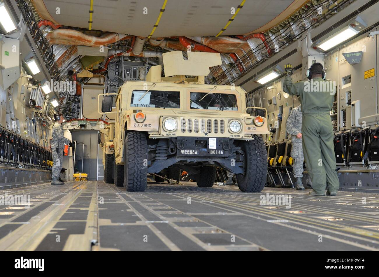 An Air Force loadmaster from the 62nd Airlift Wing at Joint Base Lewis-McChord, Wash. directs the loading of an M1151 Humvee (HMMWV) onto a C-17 Globemaster III May 7, 2018, May 7, 2018. The M1151 Enhanced Armament Carrier is an improved version of the standard HMMWV used to move troops. The movement is part of a field training exercise being conducted by the 201st Expeditionary Military Intelligence Brigade and is designed to provide more realistic load training for the Air Force and more airlift equipment preparation training for the Army. (U.S. Army photo by Staff Sgt. Chris McCullough). () - Stock Image