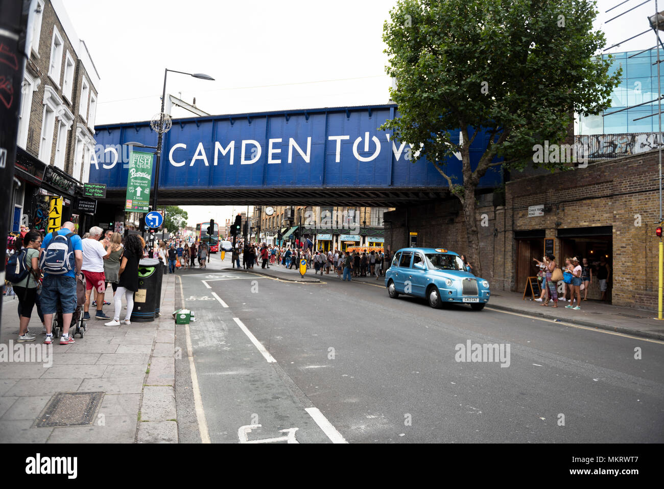 Blue taxicab drives through Chalk Farm road passing by the Camden Town railway bridge in Camden Town, London, UK. - Stock Image
