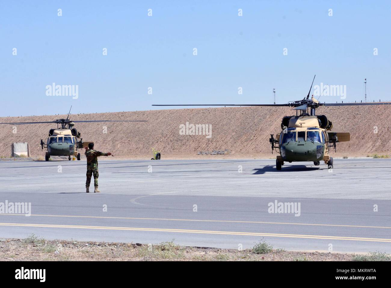 An Afghan Air Force member directs two UH-60 Blackhawks as they prepare to take off for the first Afghan-led operational mission on this aircraft May 8, 2018, Kandahar Air Field, Afghanistan, May 8, 2018. The mission, which was in support of the elections, occurred just one day after the crews graduated from Mission Qualification Training. (U.S. Air Force photo/1st Lt. Erin Recanzone). () - Stock Image