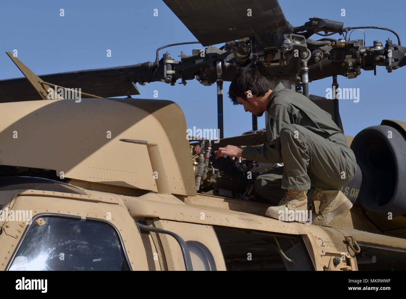 KANDAHAR AIRFIELD (May 8, 2018) -- An Afghan Air Force member inspects a UH-60 Blackhawk as air crews prepare for their first Afghan-led operational mission on this aircraft May 8, 2018, Kandahar Air Field, Afghanistan, May 8, 2018. The mission, which was in support of the elections, occurred just one day after the crews graduated from Mission Qualification Training. (U.S. Air Force photo/1st Lt. Erin Recanzone). () - Stock Image