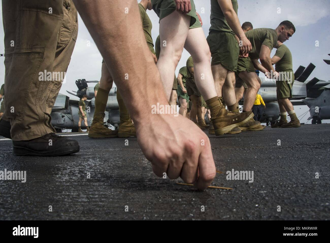 180507-N-ZG607-00112 U.S. 5TH FLEET AREA OF OPERATIONS (May 7, 2018) Marines assigned to the 26th Marine Expeditionary Unit perform a foreign object damage walk down on the flight deck aboard the Wasp-class amphibious assault ship USS Iwo Jima (LHD 7), May 7, 2018, May 7, 2018. Iwo Jima, homeported in Mayport, Fla. is deployed to the U.S. 5th Fleet area of operations in support of maritime security operations to reassure allies and partners, and preserve the freedom of navigation and the free flow of commerce in the region. (U.S. Navy photo by Mass Communication Specialist Seaman Dominick A. C Stock Photo