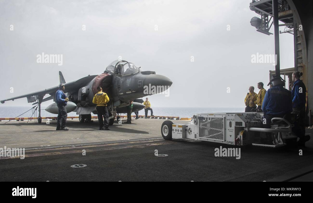180507-N-AH771-0039 U.S. 5TH FLEET AREA OF OPERATIONS (May 7, 2018) Sailors aboard the Wasp-class amphibious assault ship USS Iwo Jima (LHD 7) prepare an AV-8B Harrier jet, attached to Marine Medium Tiltrotor Squadron (VMM) 162 (Reinforced), to be moved into the ship's hangar bay, May 7, 2018, May 7, 2018. Iwo Jima, homeported in Mayport, Fla. is on deployment to the U.S. 5th Fleet area of operations in support of maritime security operations to reassure allies and partners, and preserve the freedom of navigation and the free flow of commerce in the region. (U.S. Navy photo by Mass Communicati Stock Photo