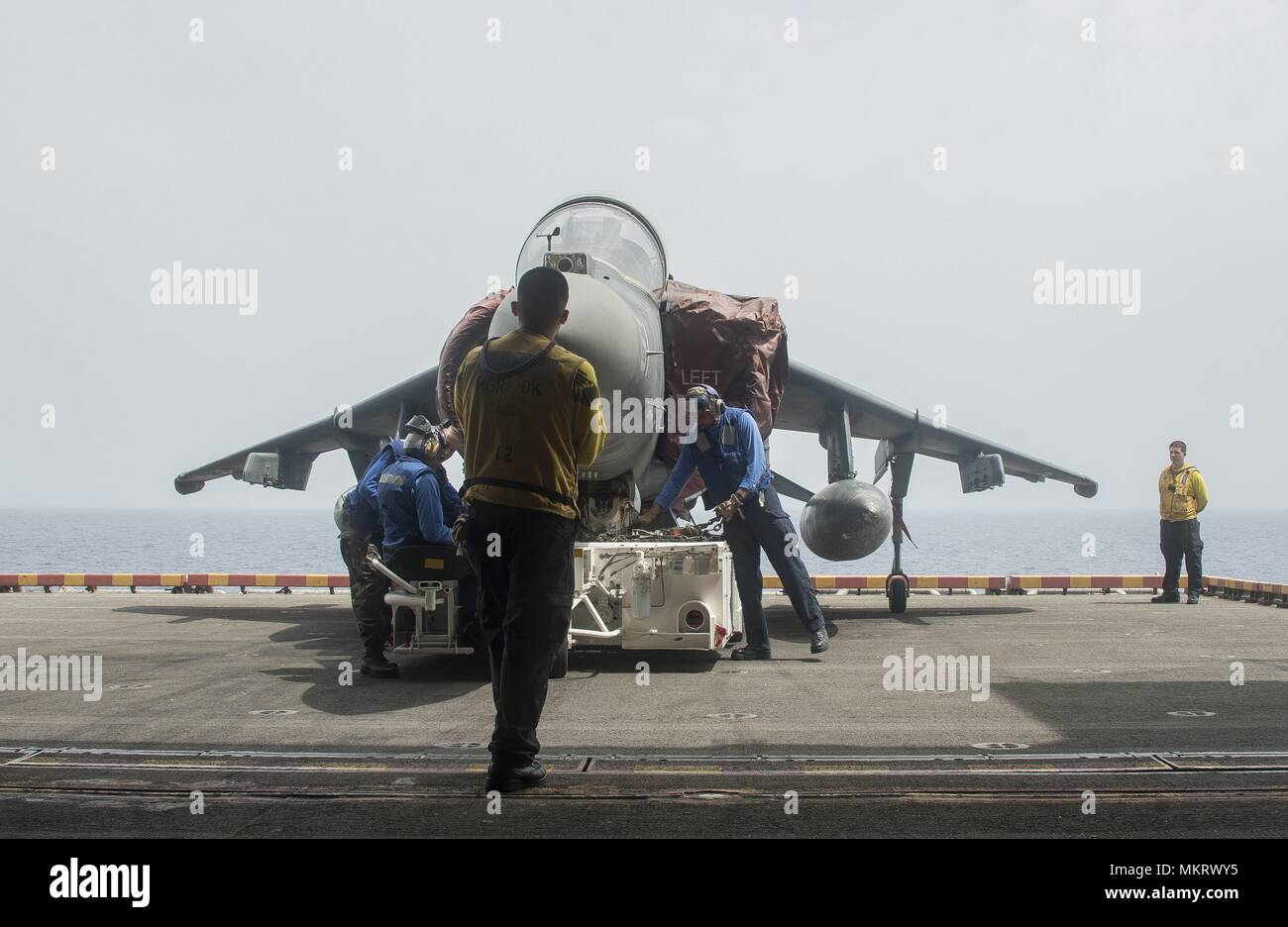 180507-N-AH771-0071 U.S. 5TH FLEET AREA OF OPERATIONS (May 7, 2018) Sailors aboard the Wasp-class amphibious assault ship USS Iwo Jima (LHD 7) prepare an AV-8B Harrier jet attached to Marine Medium Tiltrotor Squadron (VMM) 162 (Reinforced), to be moved into the ship's hangar bay, May 7, 2018, May 7, 2018. Iwo Jima, homeported in Mayport, Fla. is on deployment to the U.S. 5th Fleet area of operations in support of maritime security operations to reassure allies and partners, and preserve the freedom of navigation and the free flow of commerce in the region. (U.S. Navy photo by Mass Communicatio Stock Photo