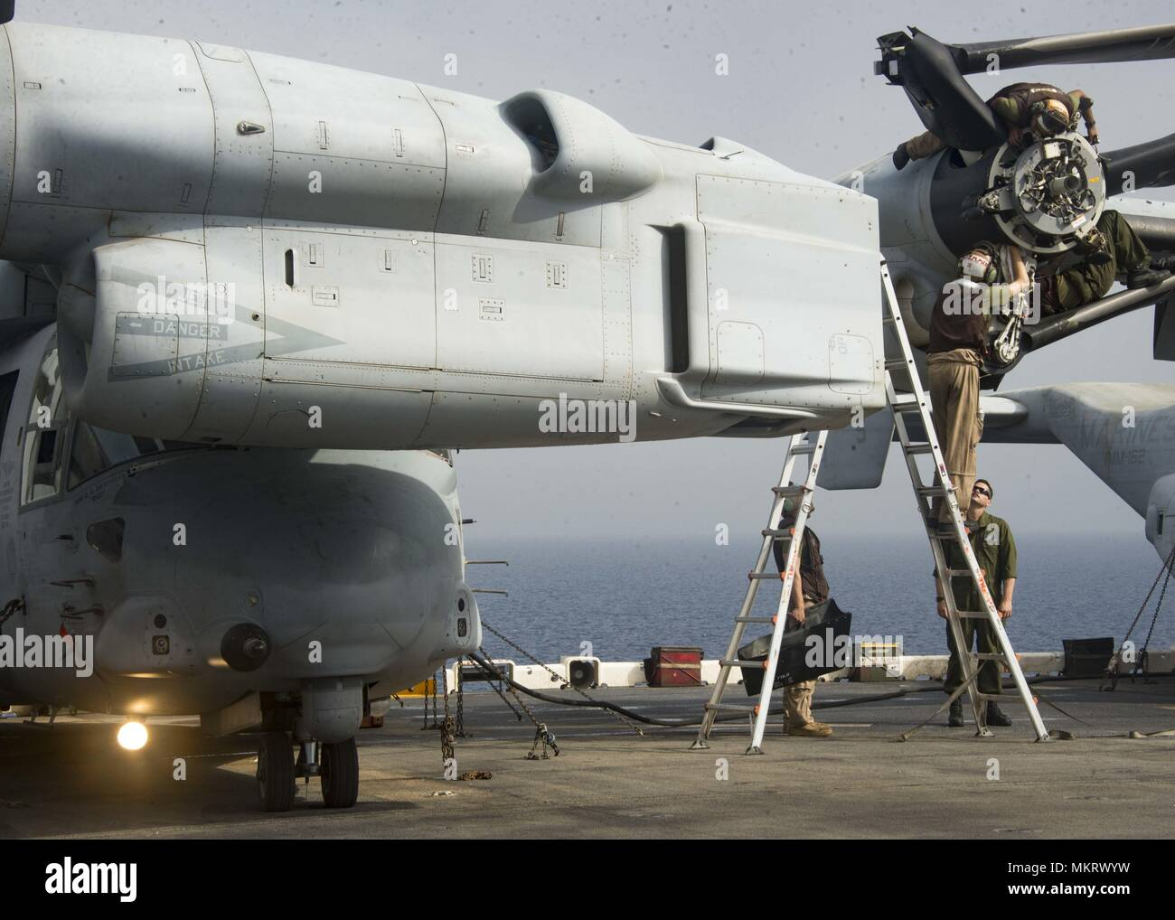 180507-N-ZG607-0102 U.S. 5TH FLEET AREA OF OPERATIONS (May 7, 2018) Marines assigned to the 26th Marine Expeditionary Unit perform maintenance on an MV-22 Osprey on the flight deck aboard the Wasp-class amphibious assault ship USS Iwo Jima (LHD 7), May 7, 2018, May 7, 2018. Iwo Jima, homeported in Mayport, Fla. is deployed to the U.S. 5th Fleet area of operations in support of maritime security operations to reassure allies and partners, and preserve the freedom of navigation and the free flow of commerce in the region. (U.S. Navy photo by Mass Communication Specialist Seaman Dominick A. Creme Stock Photo