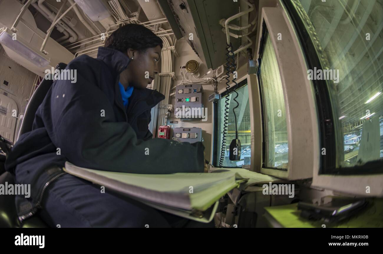 180507-N-ZK016-0010 U.S. 5TH FLEET AREA OF OPERATIONS (May 7, 2018) Aviation Boatswain's Mate (Handling) 3rd Class Charmeise Raeford, from Washington, D.C. stands watch during aircraft movement in the hangar bay aboard the Wasp-class amphibious assault ship USS Iwo Jima (LHD 7), May 7, 2018, May 7, 2018. Iwo Jima, homeported in Mayport, Fla. is on deployment to the U.S. 5th Fleet area of operations in support of maritime security operations to reassure allies and partners, and preserve the freedom of navigation and the free flow of commerce in the region. (U.S. Navy photo by Mass Communication Stock Photo