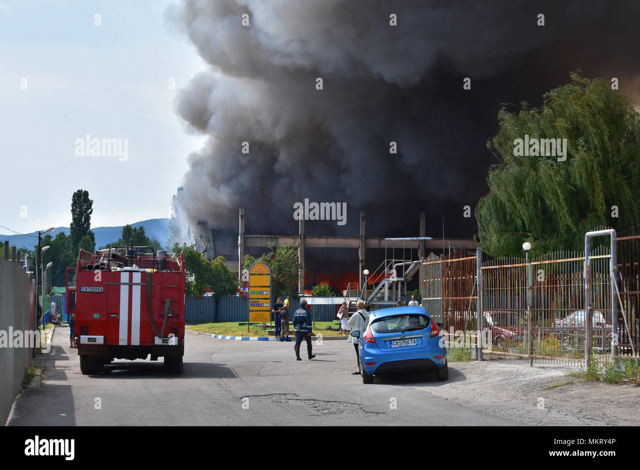 Sofia, Bulgaria - July 15, 2017: Big fire in garment warehouse right next to a petrol station in Kazichene - Sofia outskirts. Firefighters just arrive - Stock Image