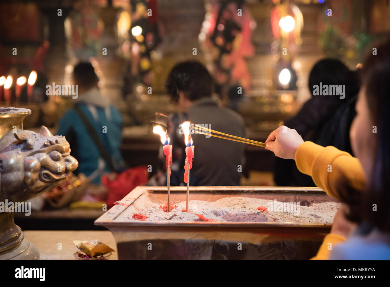 A woman lights a incense sticks from burning candles praying