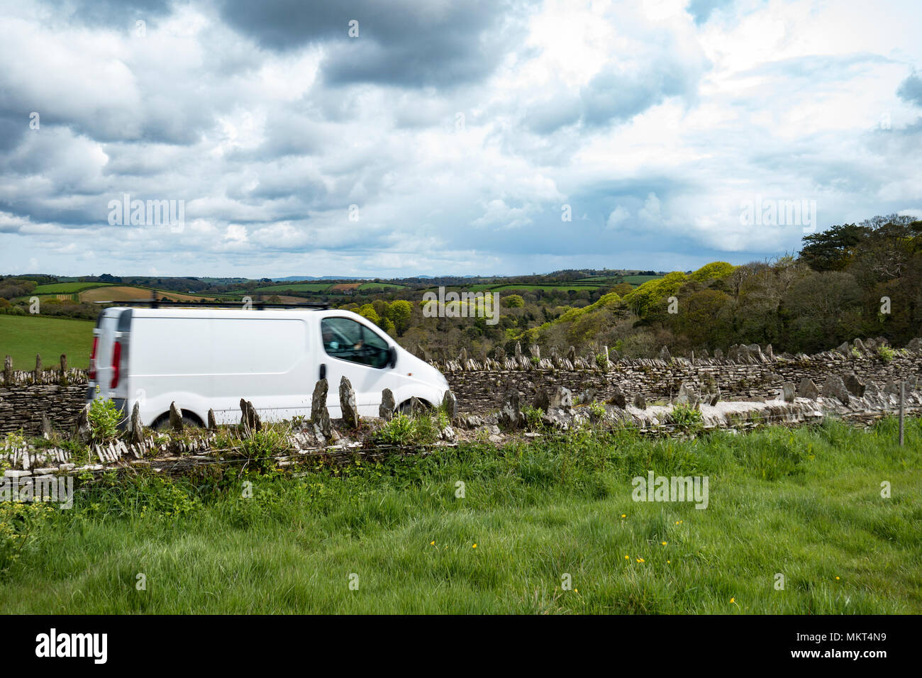 white delivery van speeding on a country lane in cornwall, england, britain, uk. - Stock Image
