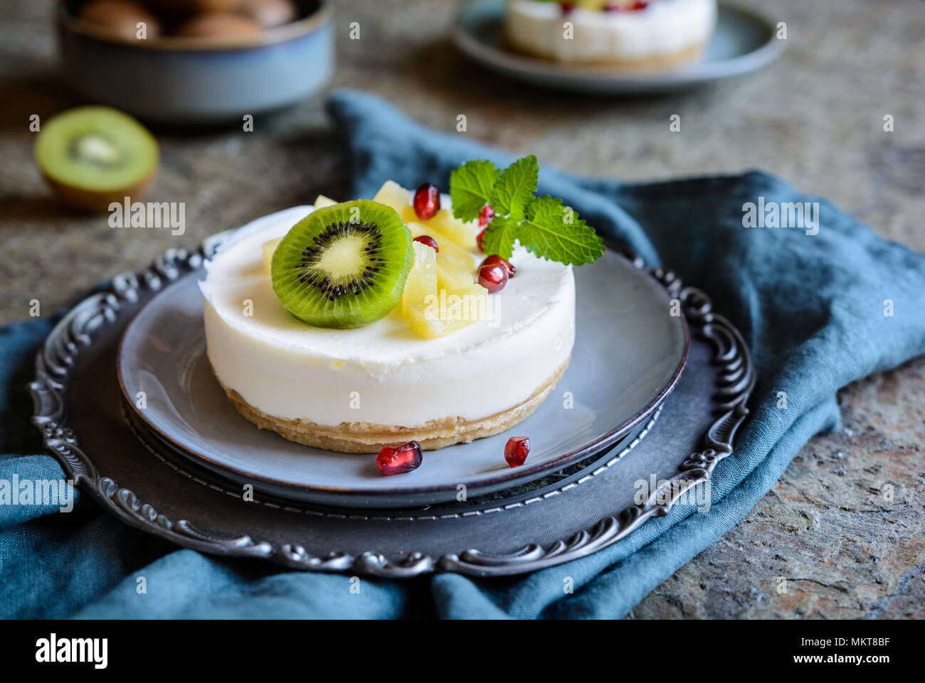 Delicious unbaked mini cheesecakes topped with pineapple, kiwi and pomegranate - Stock Image