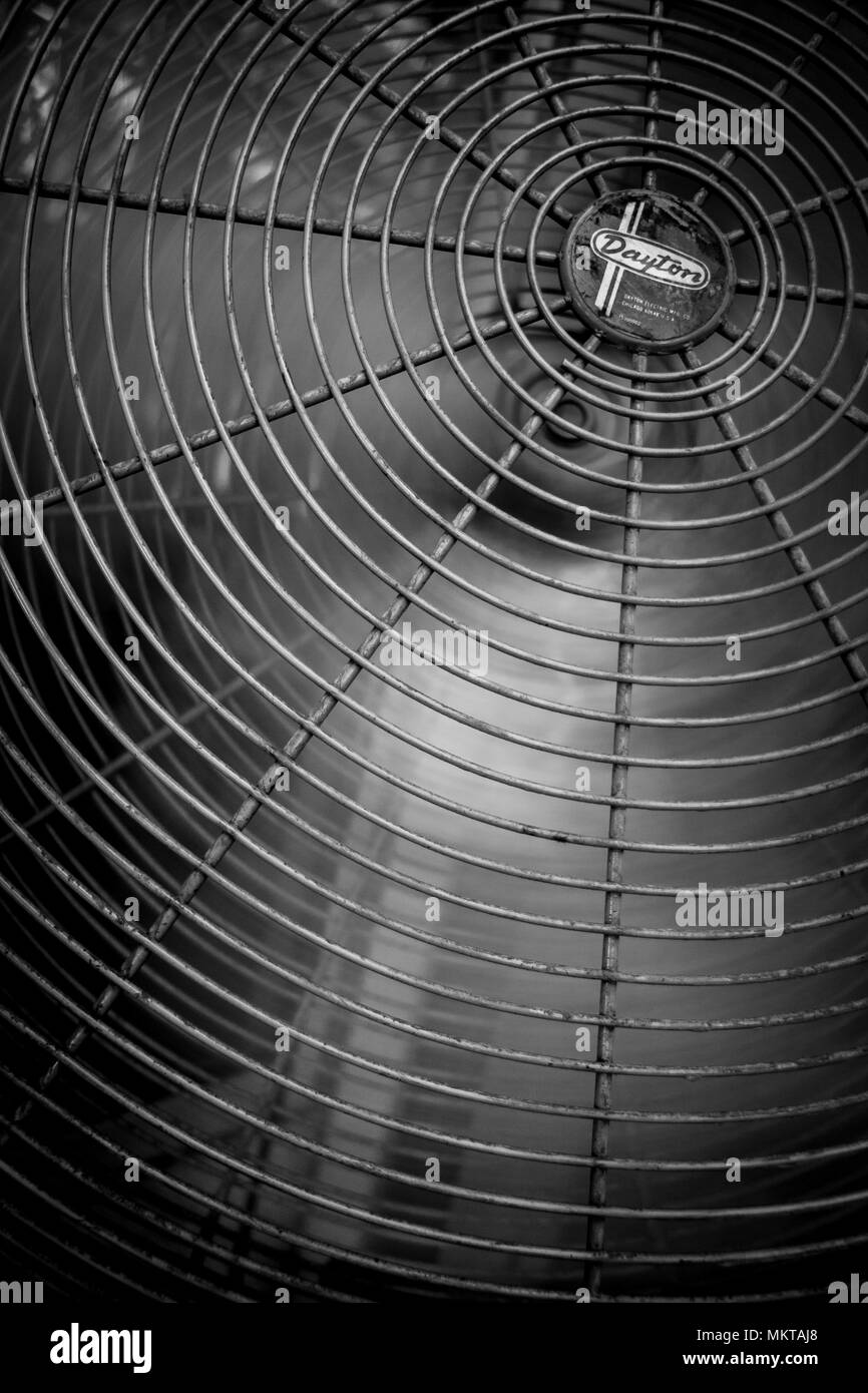 A black and white closeup of a large floor fan with its metal blades in motion - Stock Image