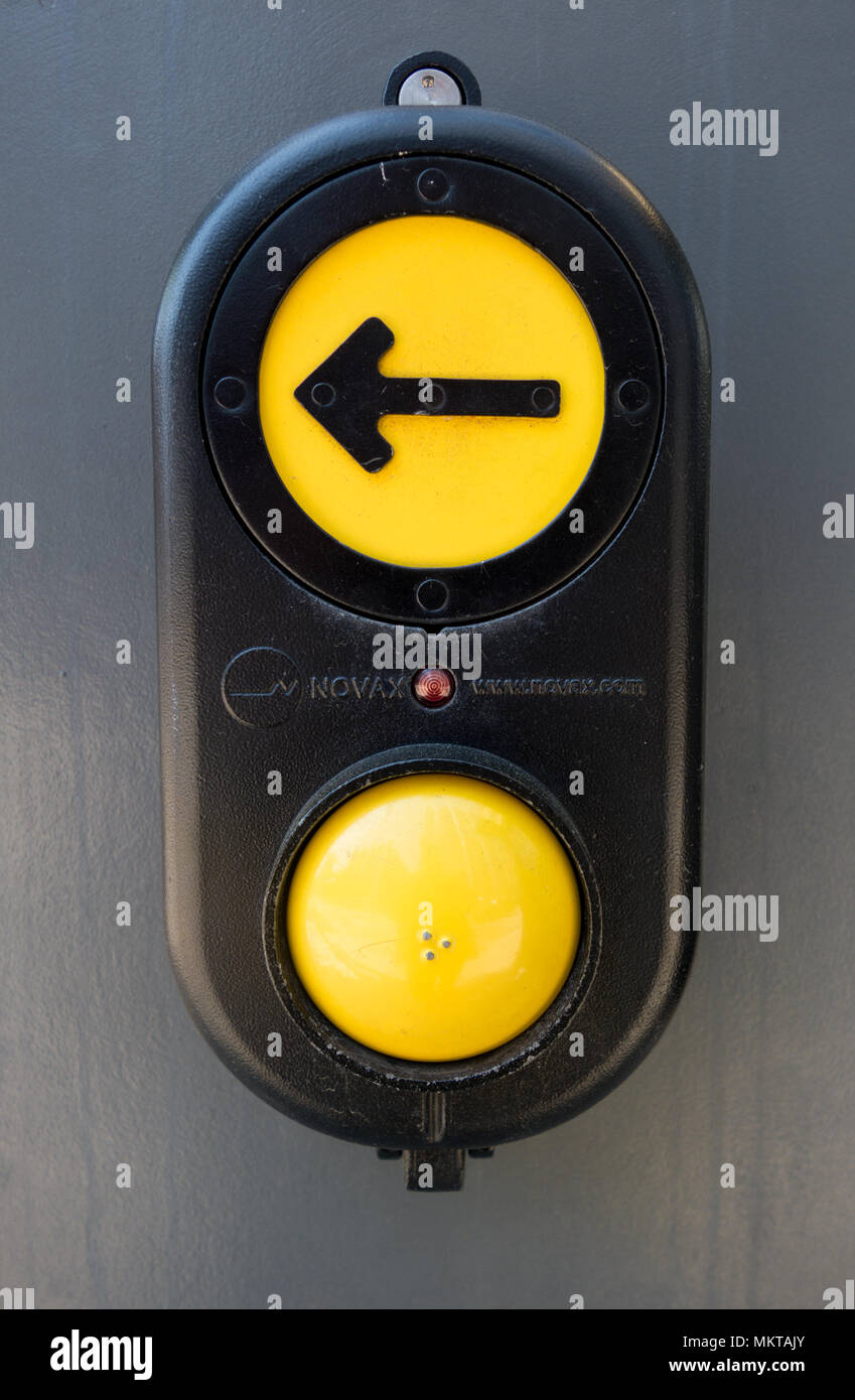 Button with arrow on a traffic signal that can be pressed to request to cross the street - Stock Image