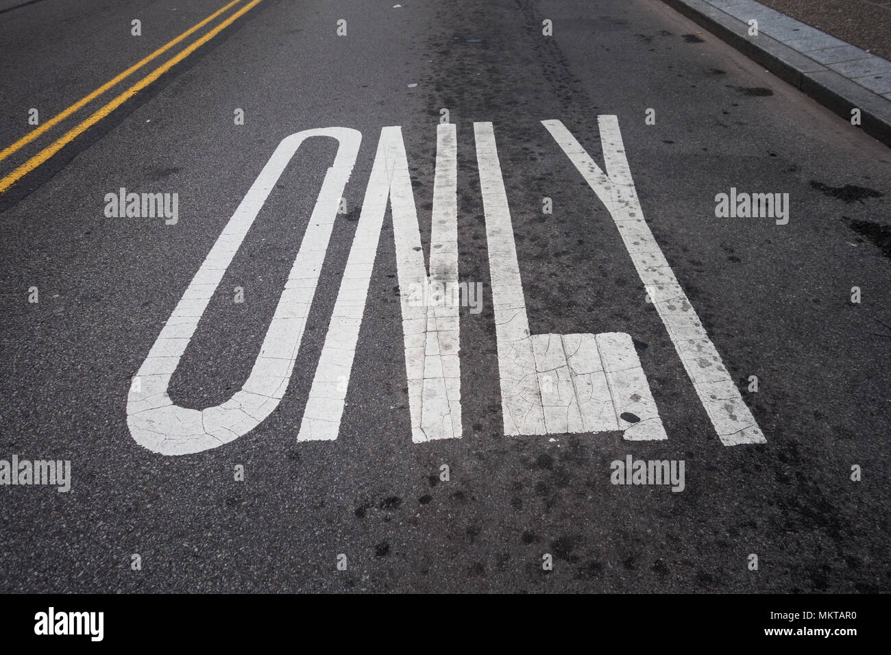 The word 'only' in capital letters painted on a road - Stock Image