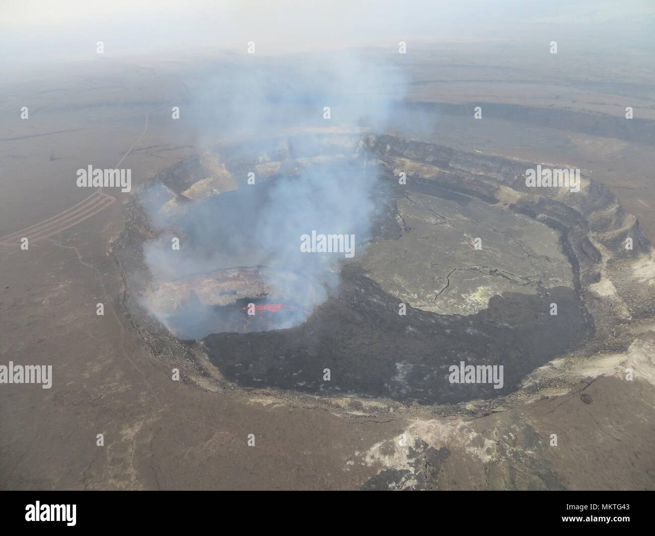 Smoke and lava rises from the Kilauea volcano following a 6.9-magnitude earthquake May 4, 2018 in Leilani Estates, Hawaii. The recent eruption continues destroying homes, forcing evacuations and spewing lava and poison gas on the Big Island of Hawaii. - Stock Image