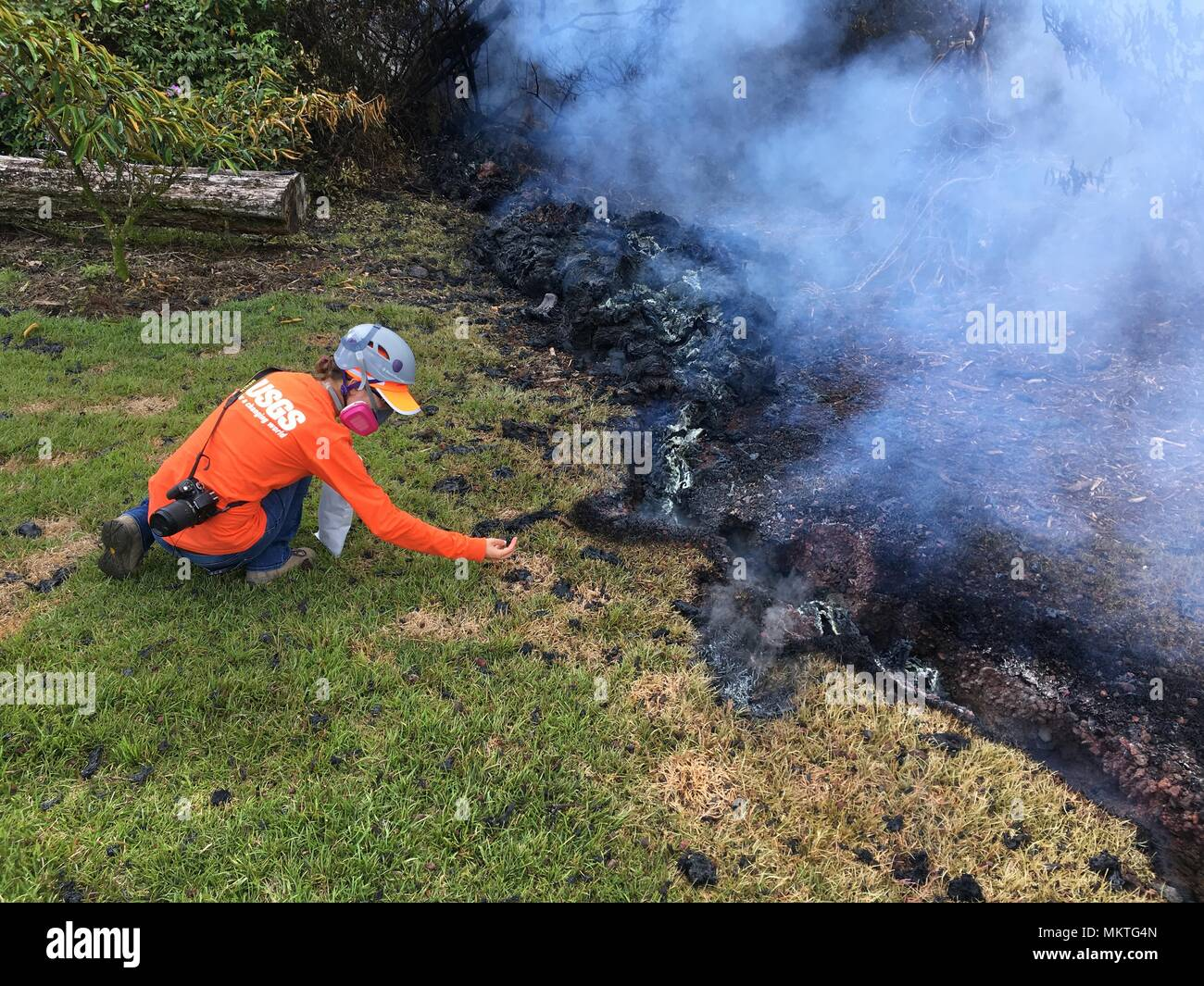 A U.S. Geologic Survey scientist gathers samples of lava splatter from the Kilauea volcanic eruption along Malama and Pomaikai Streets May 6, 2018 in Leilani Estates, Hawaii. The recent eruption continues destroying homes, forcing evacuations and spewing lava and poison gas on the Big Island of Hawaii. - Stock Image