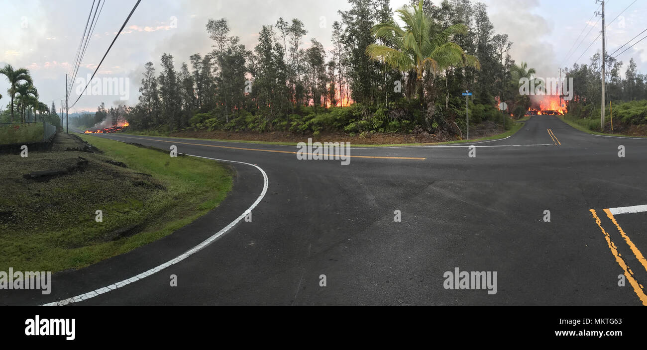 A panoramic view of lava flowing from fissure 7 near the intersection of Leilani and Makamae Streets from the Kilauea volcanic eruption May 5, 2018 in Leilani Estates, Hawaii. The recent eruption continues destroying homes, forcing evacuations and spewing lava and poison gas on the Big Island of Hawaii. - Stock Image