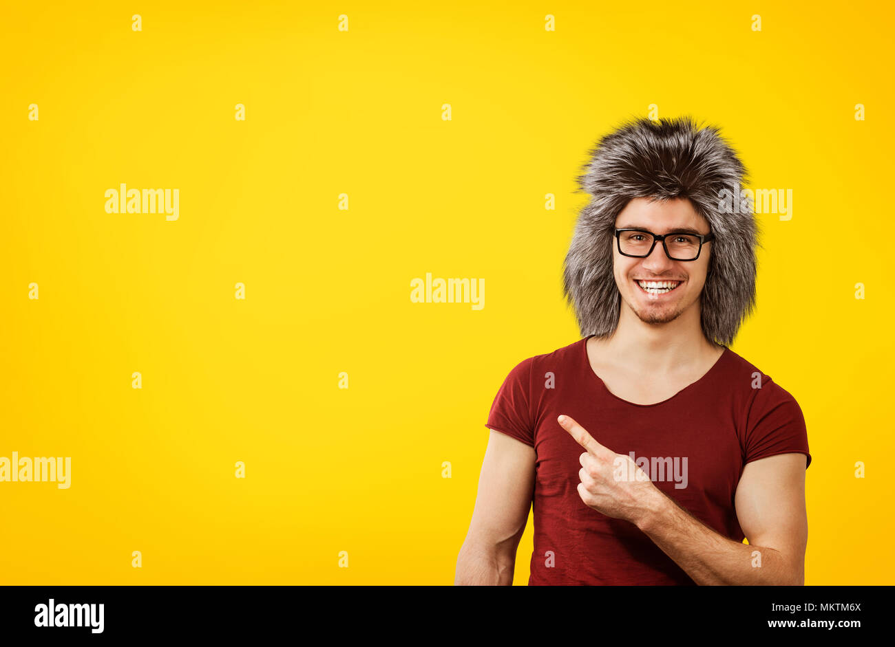 Young hipster man in glasses and winter hat pointing happily away on orange yellow background - Stock Image