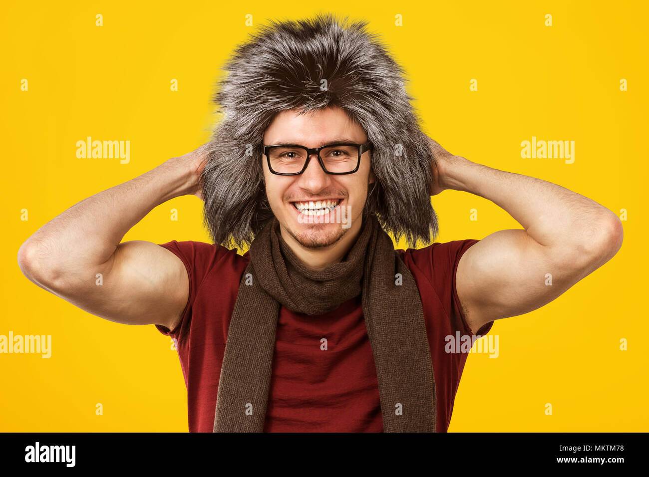 Cheerful handsome man wearing stylish furry hat and eyeglasses smiling at camera on yellow background. Stock Photo