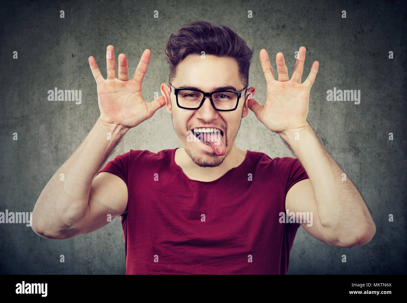 Portrait of young playful man grimacing and showing tongue on gray background. - Stock Image