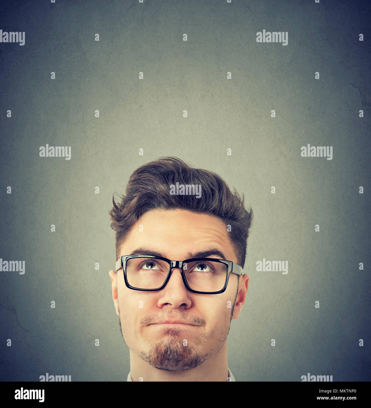 Serious young man wearing black glasses looking up thinking - Stock Image