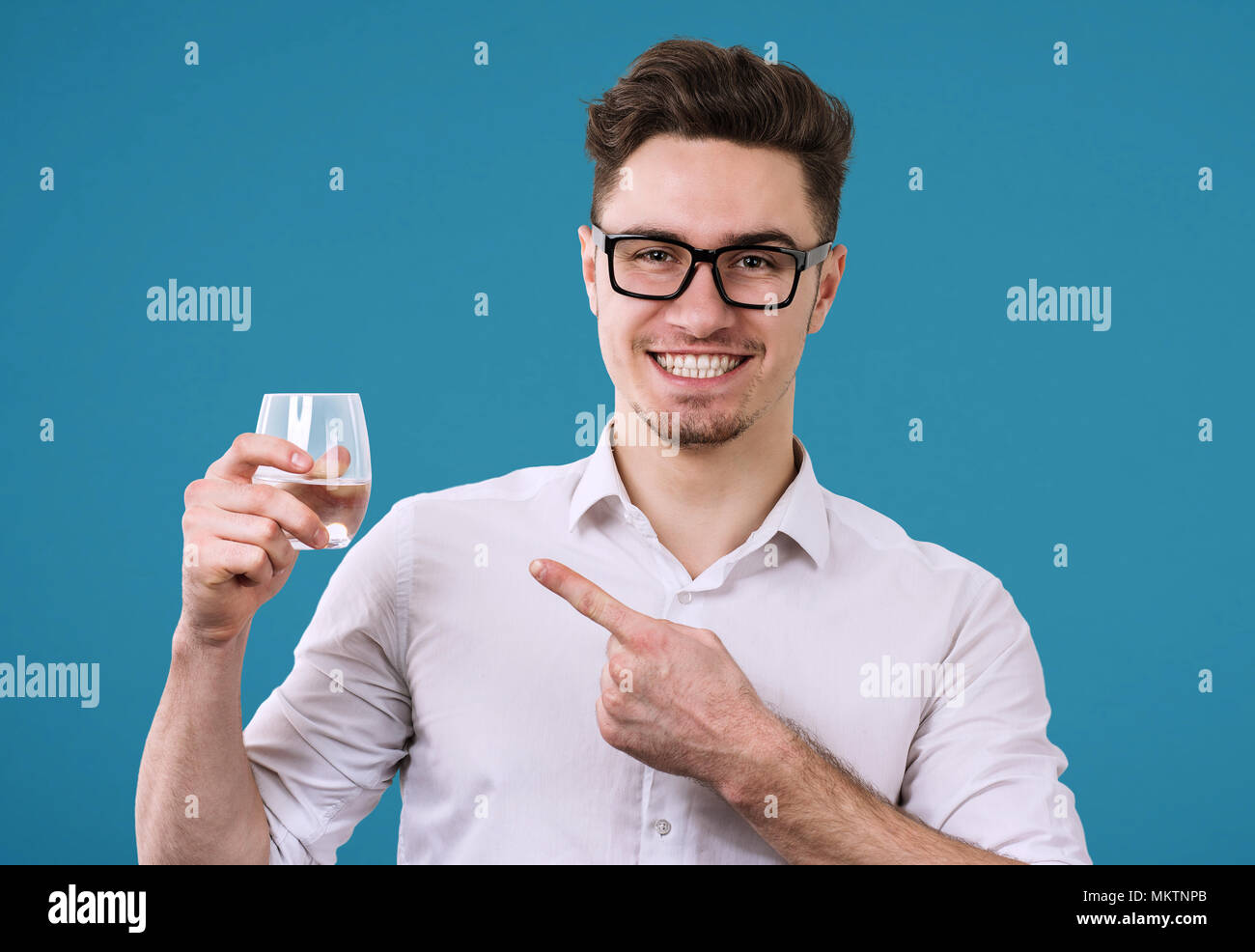 Cheerful handsome man in eyeglasses and holding glass with refreshing drink pointing at it on blue background. - Stock Image