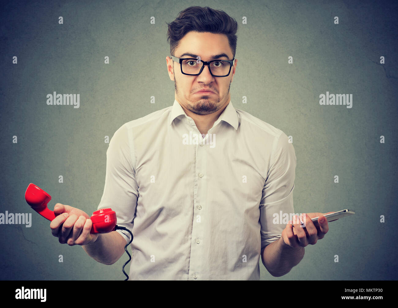 Young confused man holding old fashioned red phone and modern smarpthone looking at camera in puzzlement. - Stock Image
