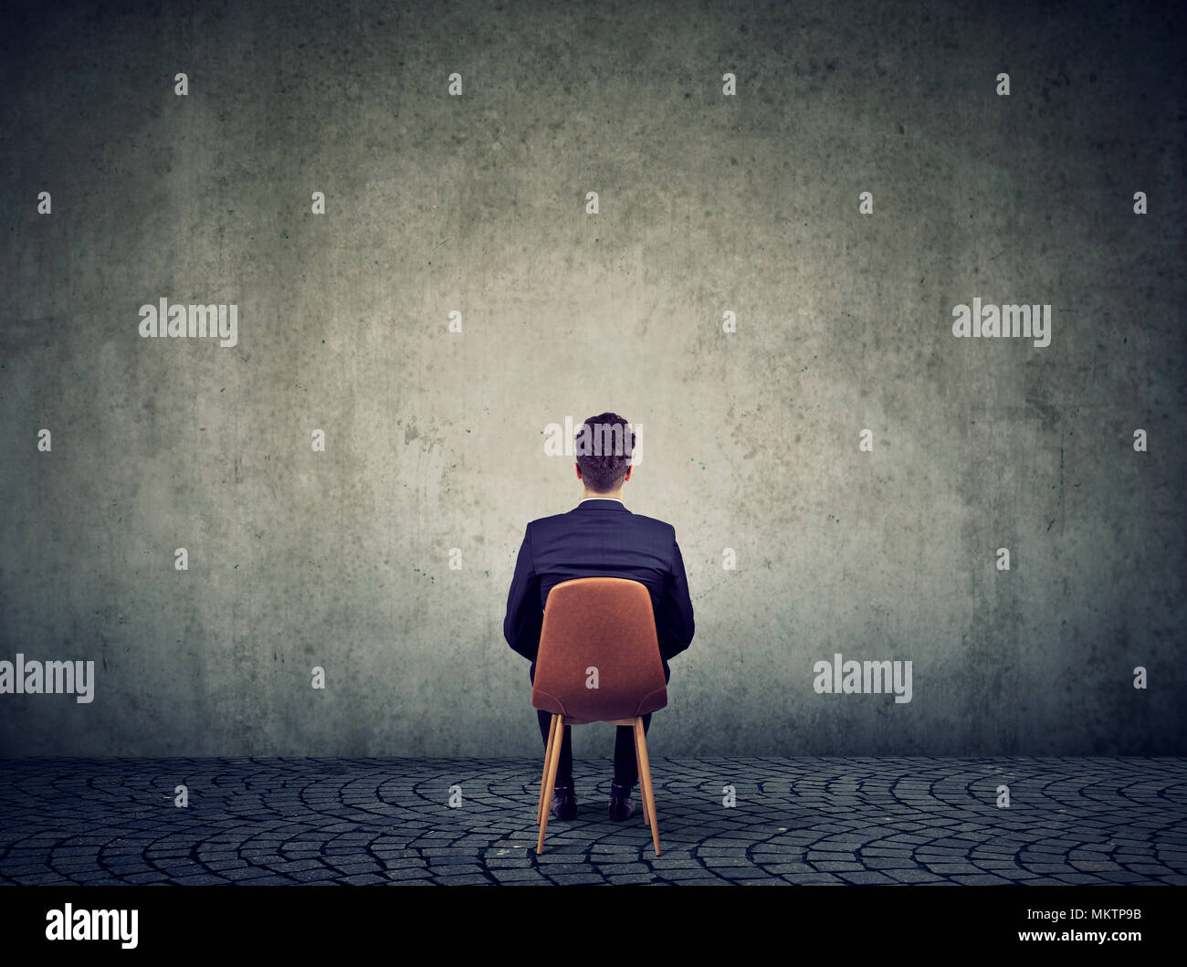 Business man sitting on chair in front of concrete empty wall solving a problem - Stock Image