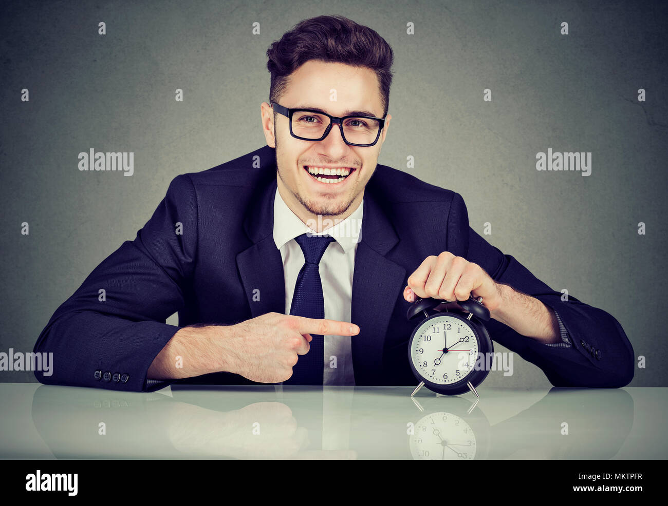 Young man in formal suit pointing at clock looking excitedly at camera happy with schedule. - Stock Image