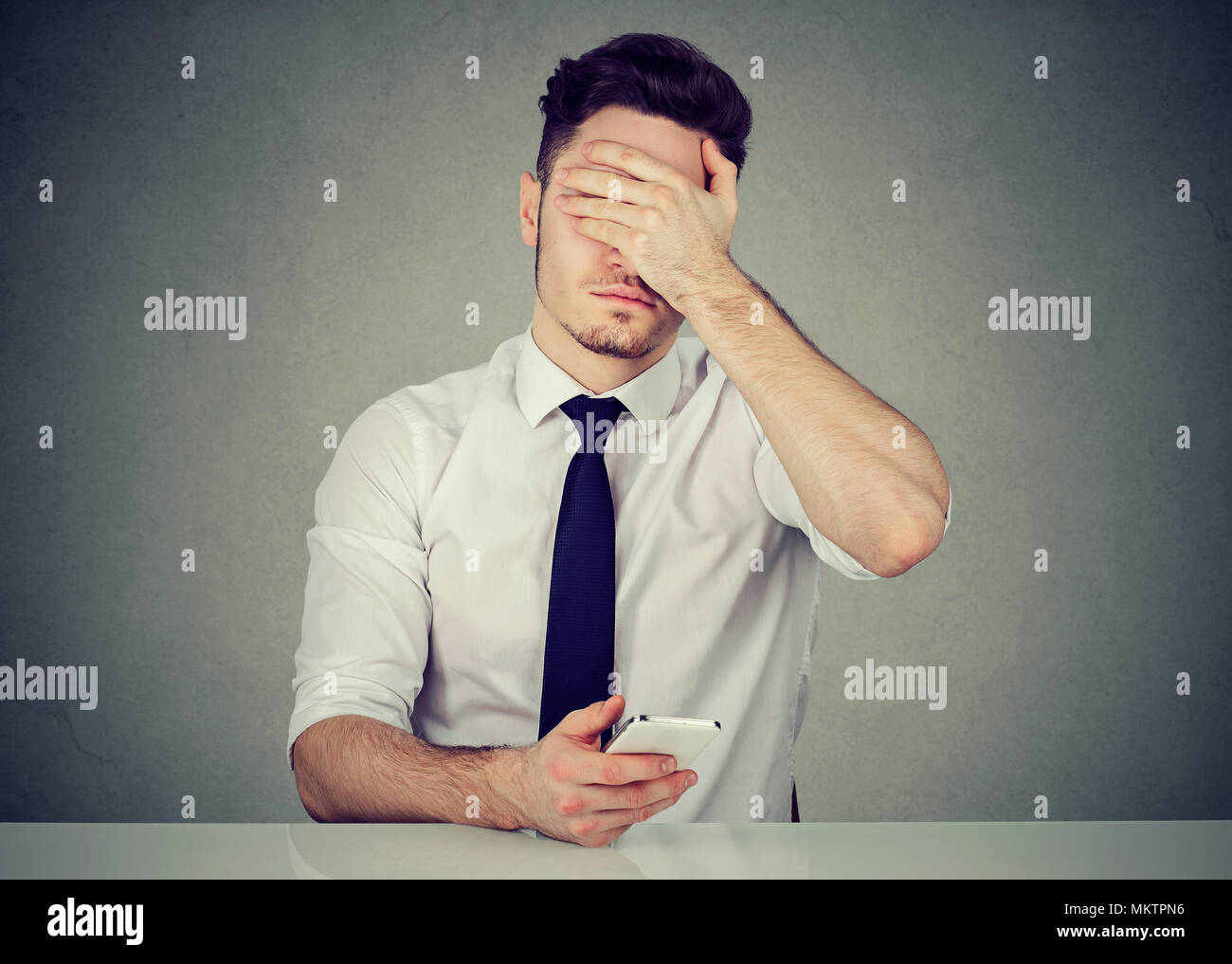 Young formal man using phone and covering face because of doing mistake while working - Stock Image