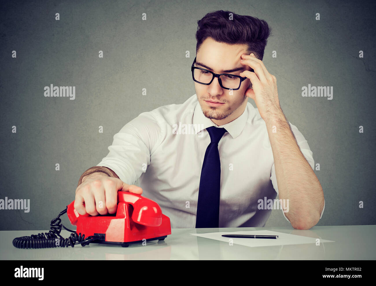 Young businessman at working table thinking carefully and making call solving problem. - Stock Image