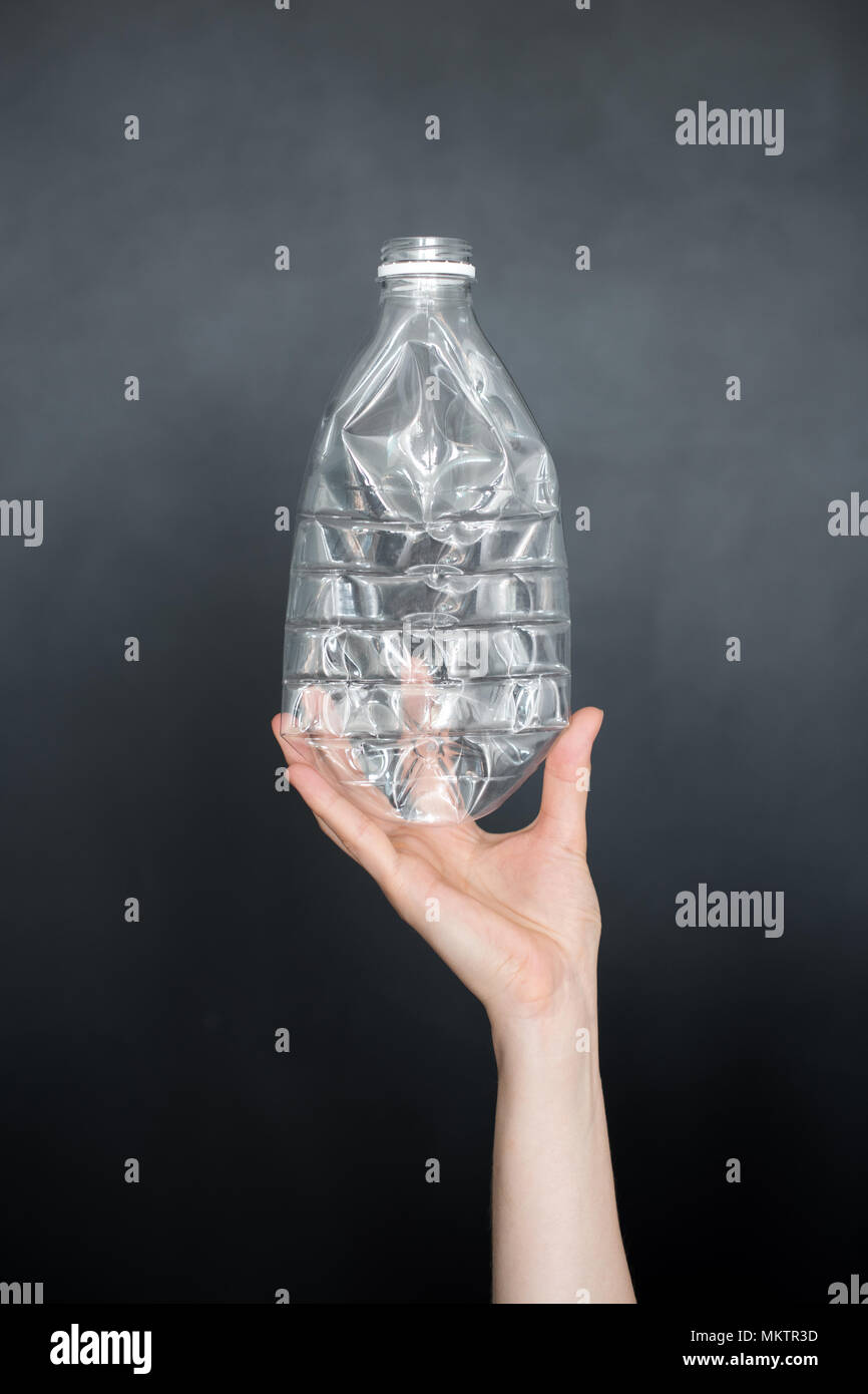 Female hand holding empty crushed plastic bottle isolated on black background. Recyclable waste. Recycling, reuse, garbage disposal, resources, enviro - Stock Image