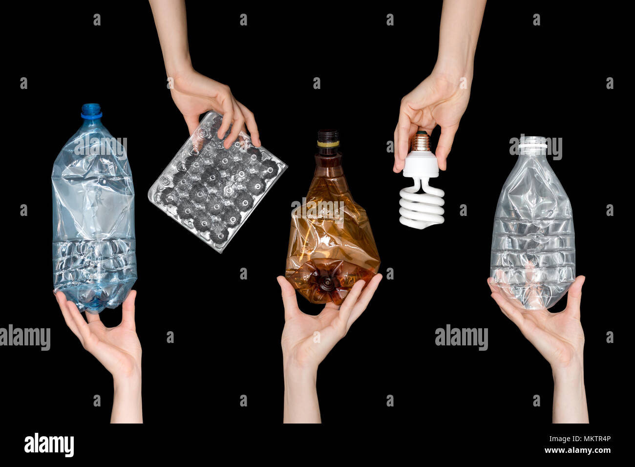 Female hands holding empty crushed plastic waste, lamp isolated on black background. Recyclable waste. Recycling, reuse, garbage disposal, resources,  - Stock Image