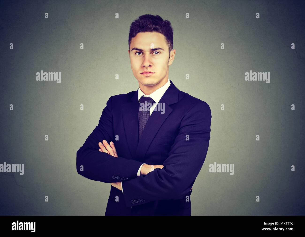 Portrait of confident businessman isolated on gray background - Stock Image