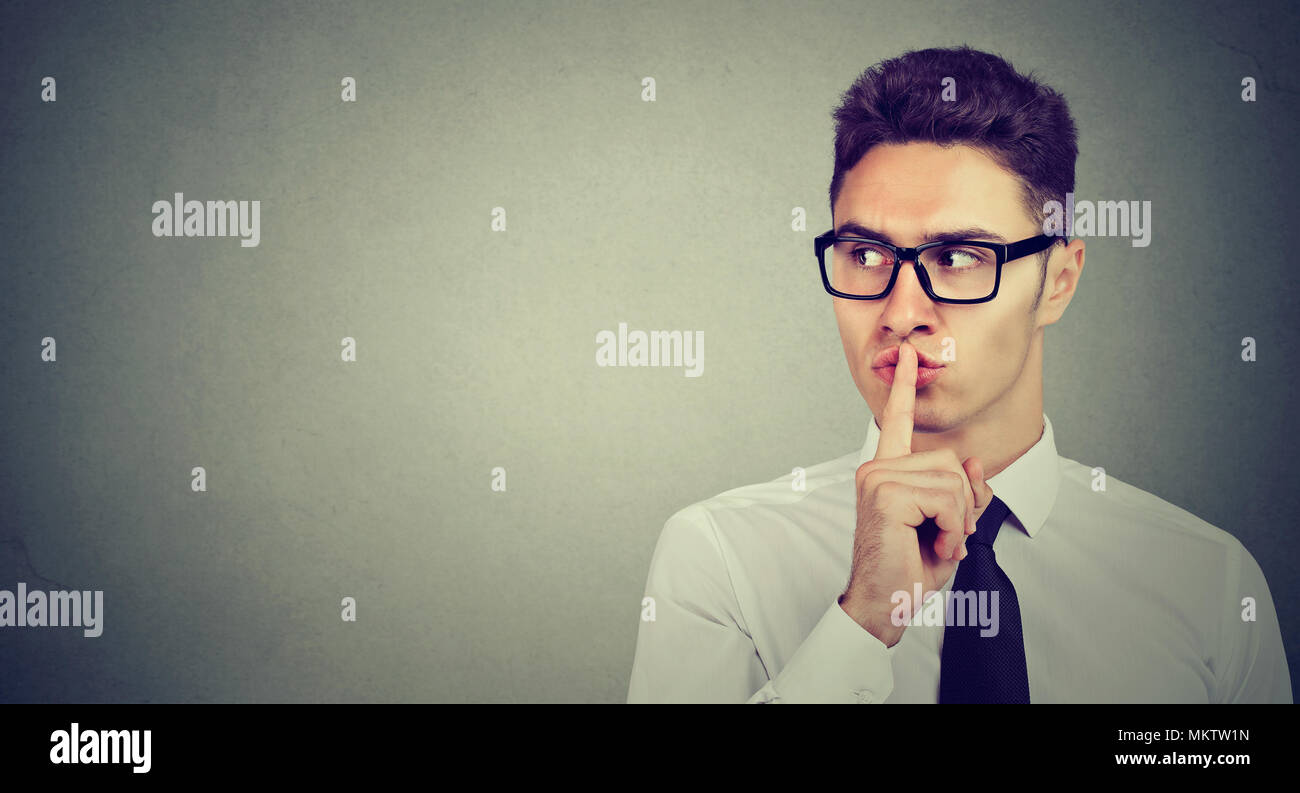 Secret guy. Man saying hush be quiet with finger on lips gesture looking to the side isolated on gray wall background. - Stock Image