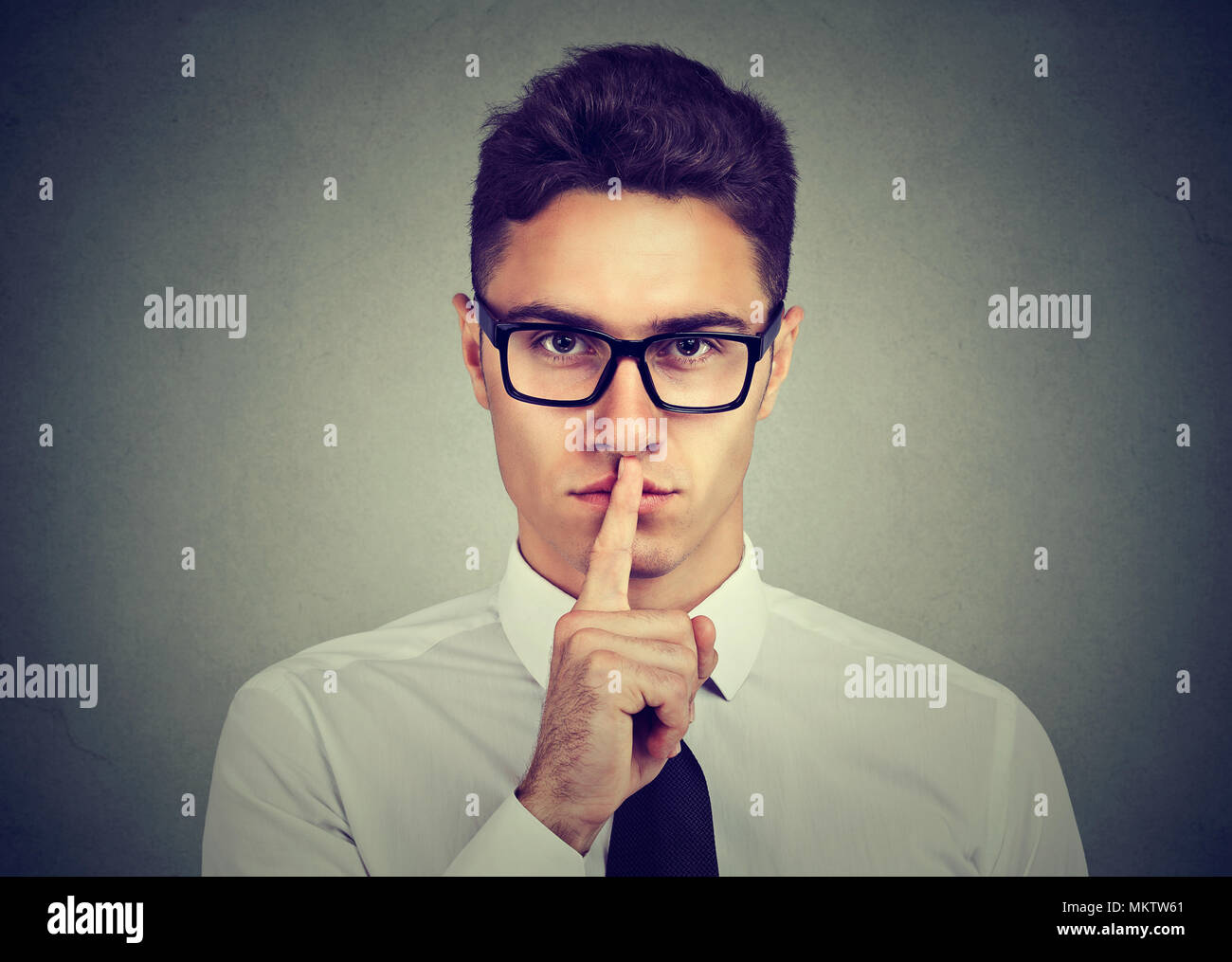 Keep my secret. Businessman holding finger on lips looking at camera standing against gray background - Stock Image