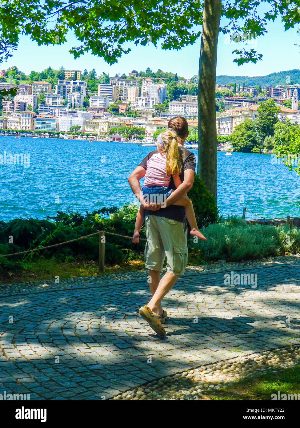 Father daughter dad child girl kid piggyback piggy back sunny summers day, family life lugano, Switzerland carefree happy living best life family love - Stock Image