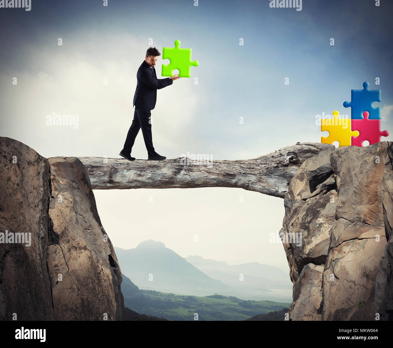 Businessman carries a piece of puzzle while he walking on a tree trunk. concept of missing piece - Stock Image