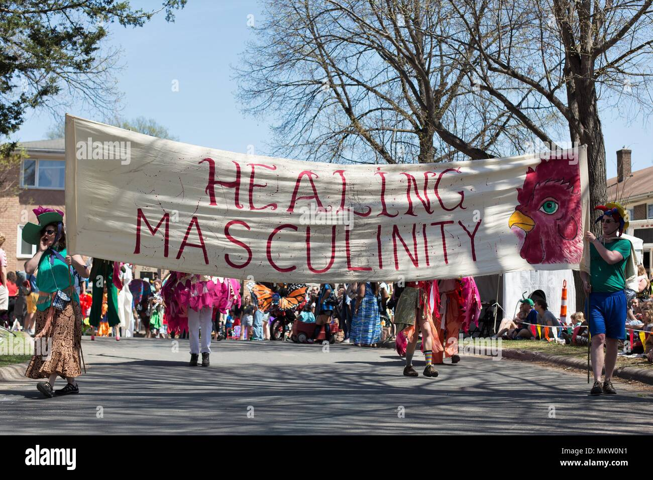 People holding a banner that reads 'Healing Masculinity' at the May Day parade and festival in Minneapolis, Minnesota, USA. - Stock Image