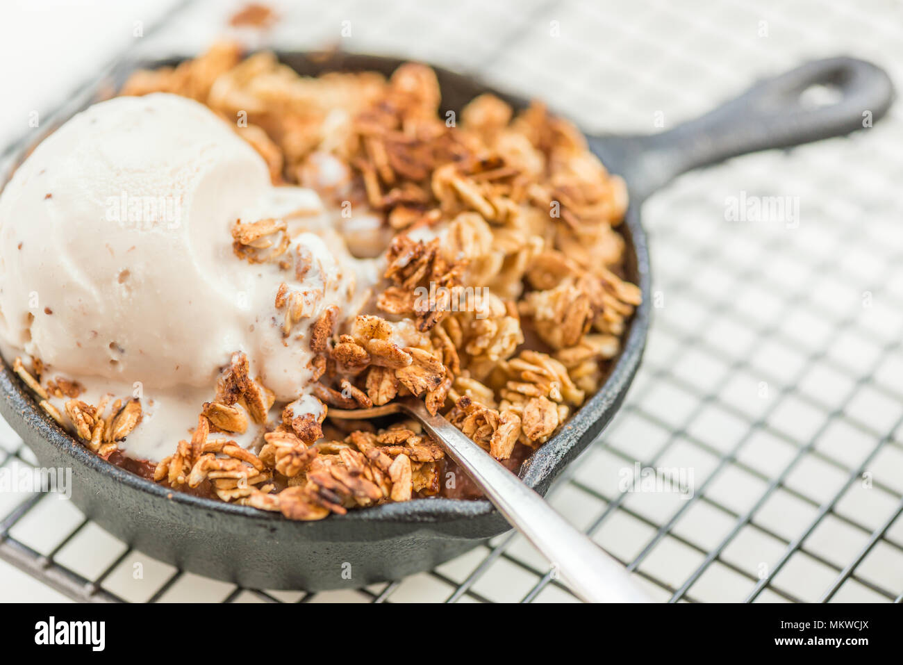 Homemade cooked rhubarb and apple crumble with oatmeal and vanilla ice cream in the iron pans - Stock Image