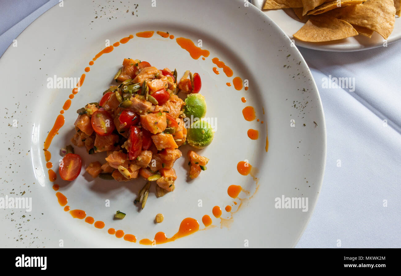 Ceviche de Salmon, spicy cold salmon salad with tomatoes and avocado - Stock Image