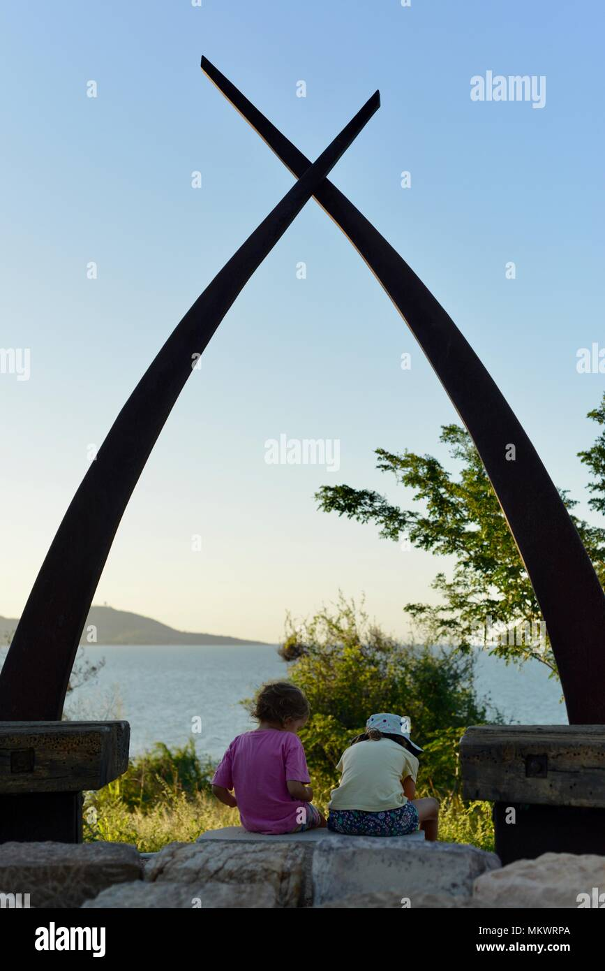 Two children sitting under a large metal and stone sculpture overlooking magnetic island,  Kissing point fort, Townsville Queensland, Australia - Stock Image