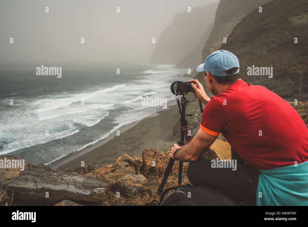 Tourist making photograph of cliff coastline with ocean waves from Cruzinha to Ponta do Sol. Huge mountains on the trekking path. Santo Antao Island, Cape Verde - Stock Image
